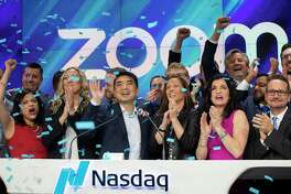 Zoom CEO Eric Yuan, center, celebrates the opening bell at Nasdaq as his company holds its IPO, Thursday, April 18, 2019, in New York. The videoconferencing company is headquartered in San Jose, Calif. (AP Photo/Mark Lennihan)