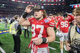 ARLINGTON, TX - DECEMBER 29: Ohio State Buckeyes defensive end Nick Bosa (#97) puts on his champions hat during the Cotton Bowl Classic matchup between the USC Trojans and Ohio State Buckeyes on December 29, 2017, at the AT&T Stadium in Arlington, TX.  Ohio State won the game 24-7.  (Photo by Matthew Visinsky/Icon Sportswire via Getty Images)
