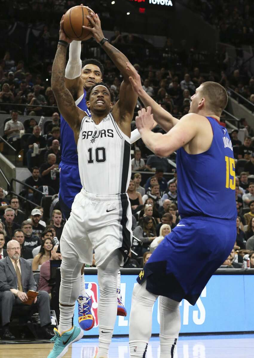 DeMar DeRozan battles through Gary Harris only to meet Nikola Jokic in the lane as the Spurs host the Nuggets in game 3 of the first round on Western Conference playoffs at the AT&T Center on April 18, 2019.