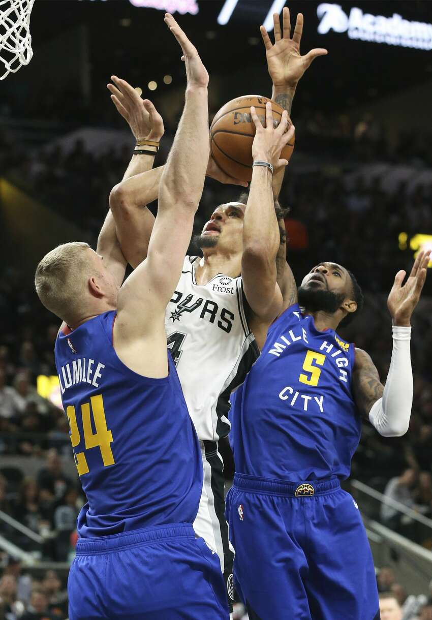 Derrick White squeezes a shot off between Mason Plumlee and Will Barton as the Spurs host the Nuggets in game 3 of the first round on Western Conference playoffs at the AT&T Center on April 18, 2019.