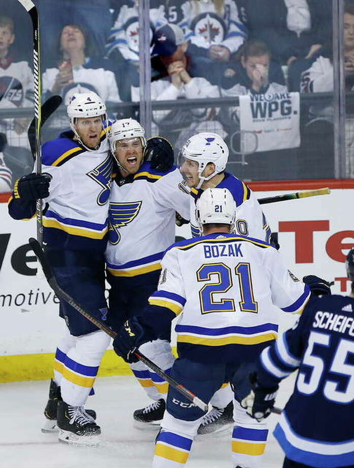 The Blues' Carl Gunnarsson (4), Jaden Schwartz (17), Alexander Steen (20) and Tyler Bozak (21) celebrate Schwartz's goal against the Winnipeg Jets in the final minute of Game 5 Thursday in Winnipeg. Photo: AP