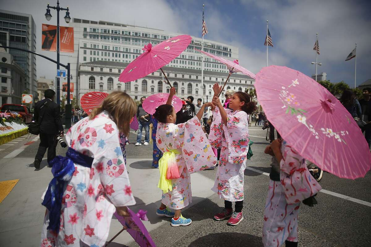 Clarendon Alternative Elementary School Japanese Bilingual Bicultural Program (JBBP) students Reina Yee (second from left) and Siena Bianchi (second from right) exchange umbrellas as they wait to walk with their school in the Cherry Blossom Festival Grand Parade on Sunday, April 19, 2015.