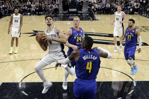 San Antonio Spurs guard Derrick White (4) drives to the basket against Denver Nuggets forward Paul Millsap (4) during the second half of Game 3 of an NBA basketball playoff series in San Antonio, Thursday, April 18, 2019. San Antonio won 118-108. (AP Photo/Eric Gay)