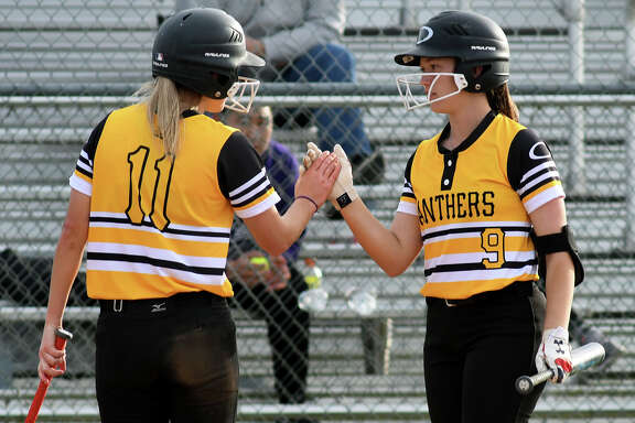 Klein Oak senior Lacy Ornelas (9) shares a high-five with senior teammate Paige Hulsey (11) after Hulsey's run scored against Memorial in their Katy ISD Softball Invitational matchup at Morton Ranch High School on Feb. 14, 2019.