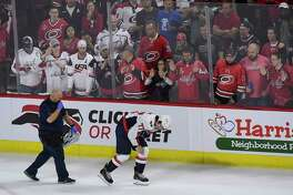 T.J. Oshie is escorted off the ice after getting injured on a hit by the Hurricanes' Warren Foegele.