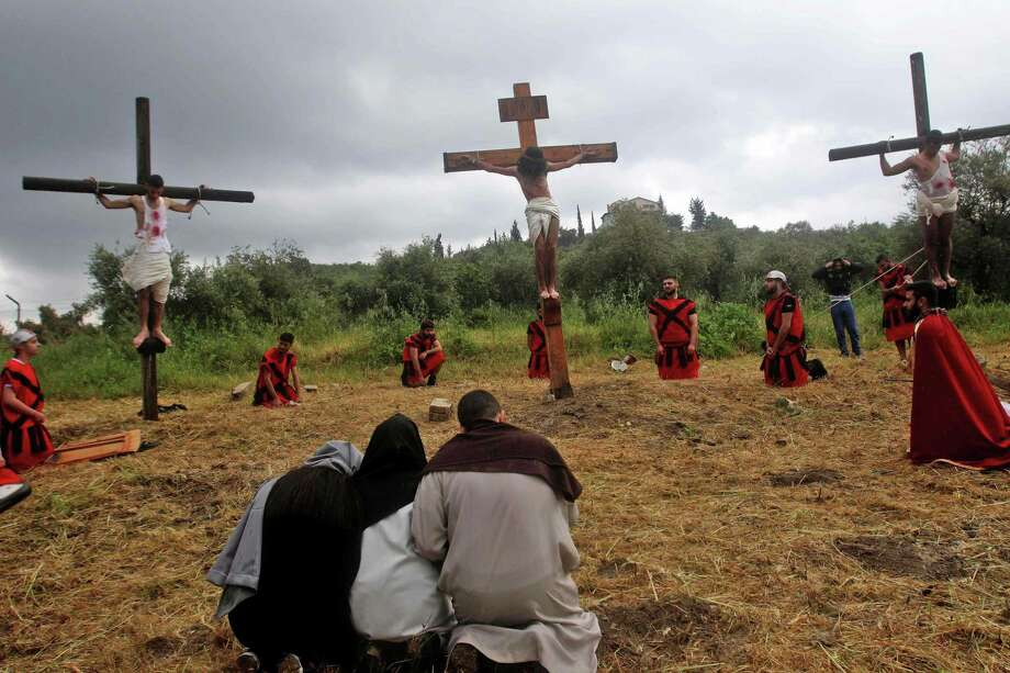 Lebanese Christian men are tied to a wooden crosses as they and fellow worshippers re-enact the crucifixion of Jesus Christ, during Good Friday celebrations in the southern Lebanese village of al-Qurayeh, near the port city of Sidon on April 19, 2019. Photo: Getty Images / AFP or licensors