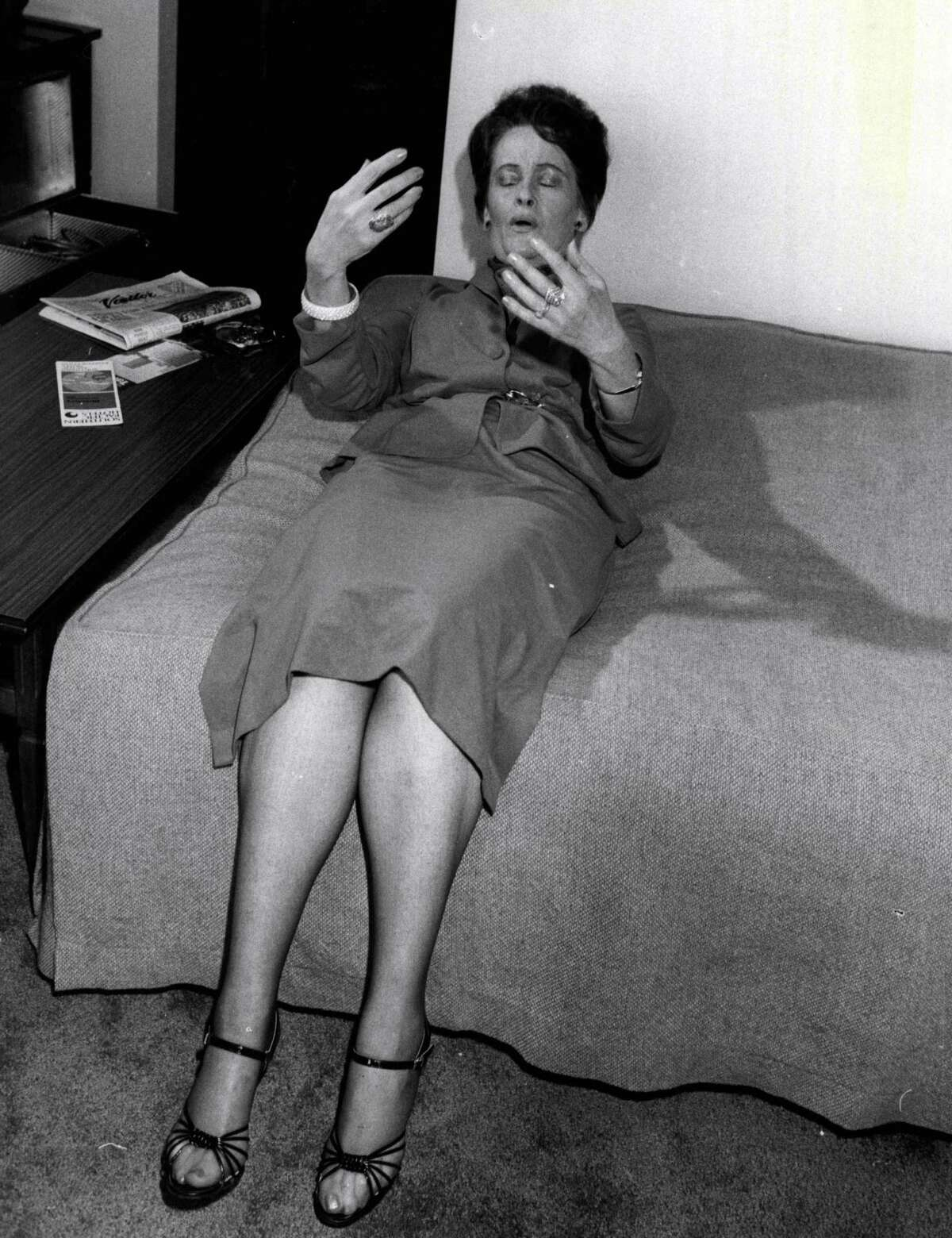 American ghost hunter, Mrs. Lorraine Warren shows how she lay back on a bed in the home of Mrs. Wendy Evans of Gladesville, and that she felt vibrations.