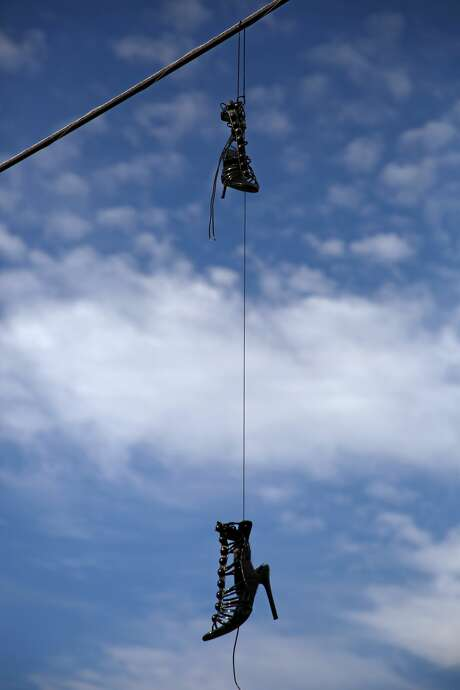 A pair of stilettos hang from an electrical wire on Plainfield Street. Houston Police run regular undercover vice operations on the Bissonnet Track to address rampant street prostitution. Photo: Godofredo A. Vásquez/Staff Photographer