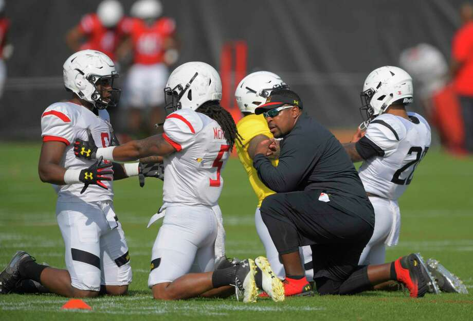 Running backs coach Elijah Brooks, kneels with Tayon Fleet-Davis, left, Anthony McFarland, 2nd left, and Javon Leake, right, during Maryland's spring football practice in College Park, Md., on April 18, 2019. MUST CREDITL Washington Post photo by John McDonnell Photo: John McDonnell, The Washington Post / The Washington Post