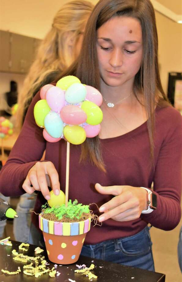 In floral design class at Needville High School, sophomore Chloe Zamarron puts the finishing touches on the Easter egg tree centerpiece she made. Photo: Needville ISD / Needville ISD