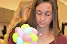 In floral design class at Needville High School, sophomore Chloe Zamarron puts the finishing touches on the Easter egg tree centerpiece she made.