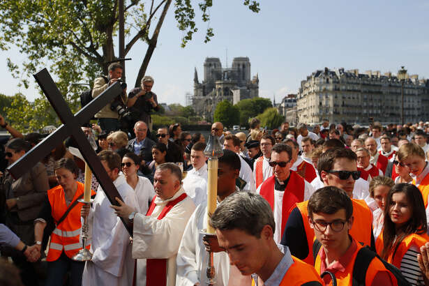 With Notre Dame cathedral in background, religious officials carry the cross during the Good Friday procession in Paris. Top French art conservation officials say the works inside Notre Dame didn't suffer major damage in the fire that devastated the cathedral, and the pieces have been removed from the building for their protection.
