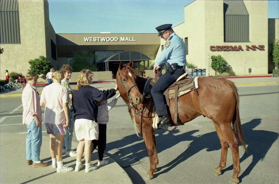 In this photo from 1988, an off-duty Houston police patrolman and his personal horse, Mike, meet with shoppers as he patrols a Westwood Mall parking lot. (Staff file photo) / Houston Chronicle
