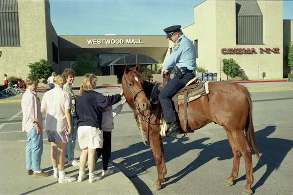 In this photo from 1988, an off-duty Houston Police patrolman and his personal horse, Mike, meet with shoppers as he patrols a Westwood Mall parking lot. (Staff file photo)