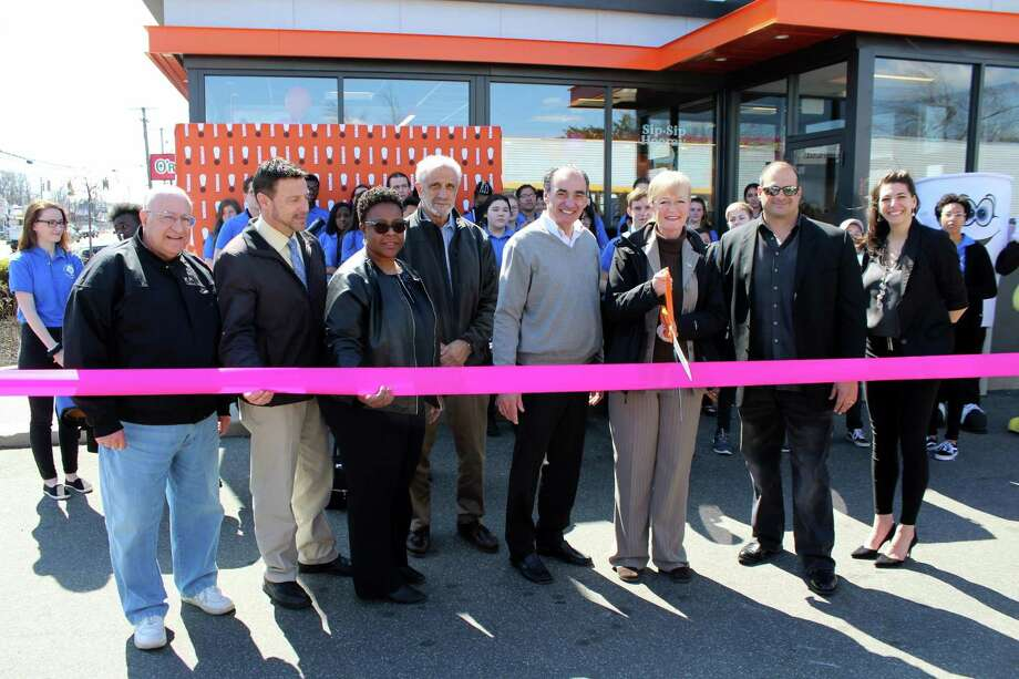 """DUNKIN' DOES IT: Accompanied by members of the West Haven High School Band, Mayor Nancy R. Rossi cuts the ceremonial ribbon April 3 with city officials and the owners of the Dunkin' Donuts franchise at 985 Boston Post Road to celebrate the restaurant's reopening as a next-generation Dunkin' concept store. From left are Councilman Peter V. Massaro, D-6; City Council Chairman Ronald M. Quagliani, D-At Large; Councilwoman Robbin Watt Hamilton, D-5; mayoral Executive Assistant Lou Esposito; and owners Frank D'Andrea, his son, Francesco D'Andrea, and his daughter, Nicole Ball. The freshly remodeled Dunkin' is the brand's restaurant of the future and the third next-generation location in Connecticut, behind Simsbury and Wallingford. For the new prototype, known as Dunkin' Next Generation, the Canton, Mass.-based doughnut and coffee chain has dropped """"Donuts"""" from its signage. The West Haven Dunkin' is the state's first location, however, to receive next-generation improvements inside as well as enhancements outside, including LED lighting. The 2,650-square-foot restaurant features a modern atmosphere and new and innovative technologies and design elements. It includes a bar-style, cold-brew tap system that pours eight coffees and teas, along with an expanded grab-and-go selection for bottled beverages and snacks. Photo: Contributed Photo / Michael P. Walsh - City Of West Haven"""