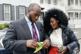 Tiana Logan shows her husband, David Logan, a check that was donated by an anonymous reader on Thursday, April 18, 2019 at the Logan's old apartment on Hamilton Street in Albany, NY. (Phoebe Sheehan/Times Union)