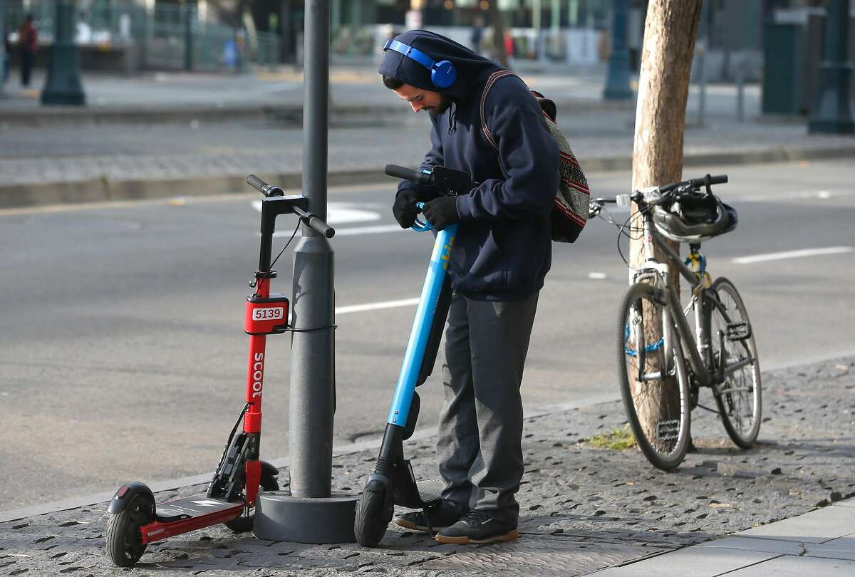 A commuter parks an e-scooter on King Street in San Francisco, Calif. on Tuesday, March 19, 2019.