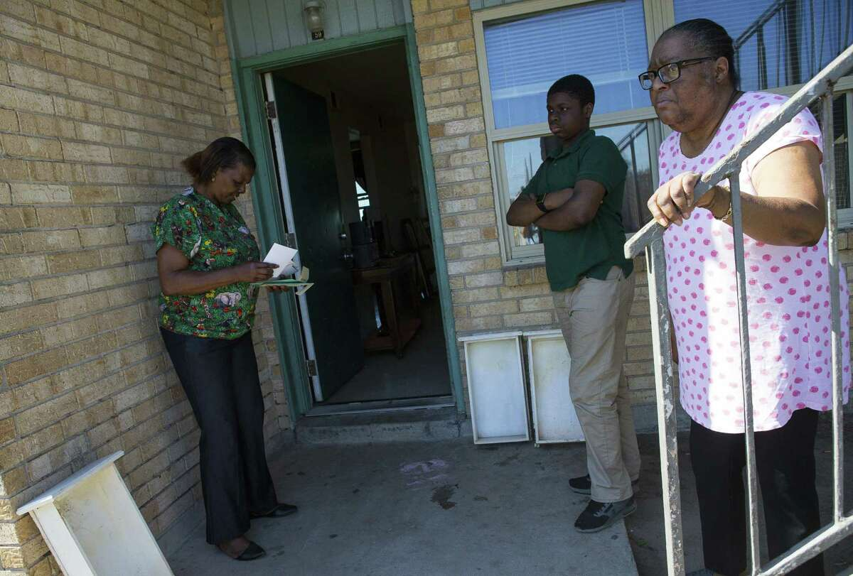 Cynthia Minix (left) and Jessie Jordan (right) wait outside Minix's apartment as workers try to stop wastewater backing up into Minix's home.