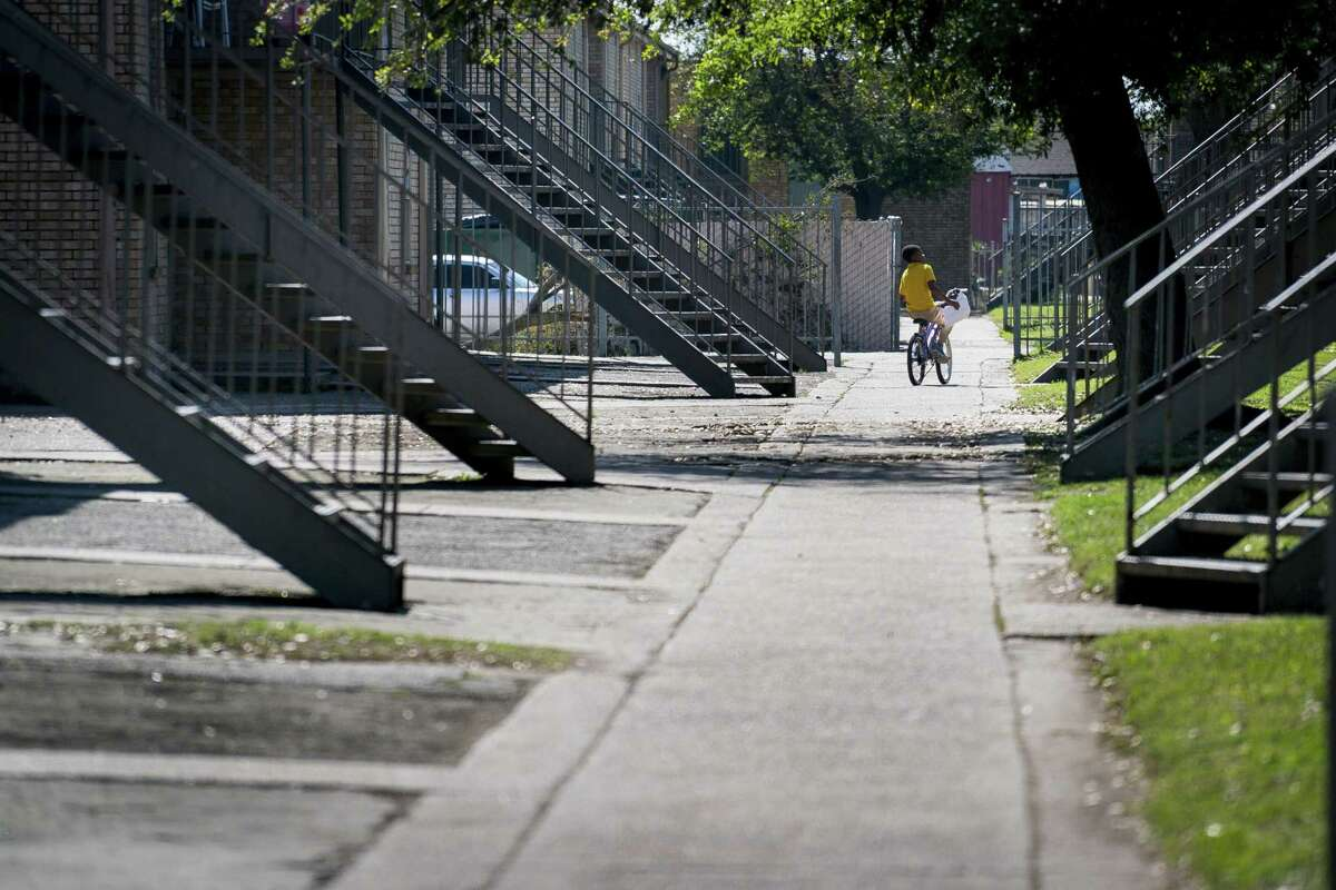 A boy rides his bicycle through the Sandpiper Cove apartments in Galveston. The complex is privately owned but receives rent subsidies from HUD.