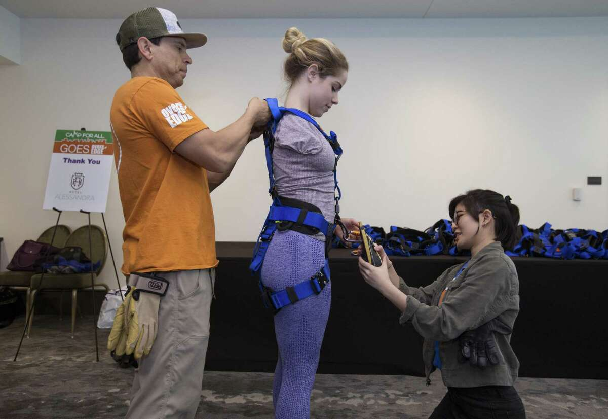 Over the Edge Staging Manager Anthony Zamora and ropes volunteer Nhu Nguyen assist Faith Malton suiting up to propel down from the 21st floor of Hotel Alessandra on Saturday, April 13, 2019, in Houston. The 22-year-old University of Houston student was born with one arm and participated in the annual fundraiser to raise money forCamp For All. Zamora added one extra rope to tighten the right side of Malton's body.