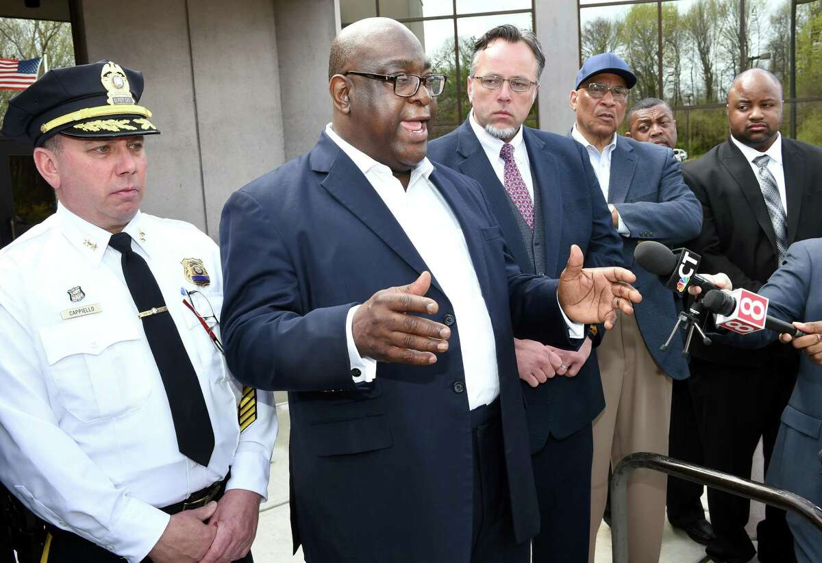 Rev. Boise Kimber, center, flanked by Hamden Acting Police Chief John Cappiello, left, and Hamden Mayor Curt Leng addresses the media outside the Hamden Government Center Friday after a meeting between the town officials and local clergy concerning the recent shooting by a Hamden police officer.