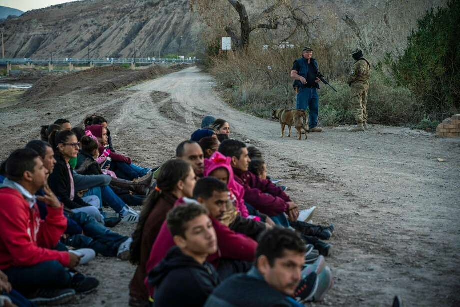 "Property owner Jeff Allen, 56, (rear left) stands near a group of about 30 Brazilian migrants, who had just crossed the border at his property in Sunland Park, New Mexico on the US-Mexico border on March 20, 2019, as they wait for US Border Patrol to pick them up. - The militia members say they will patrol the US-Mexico border near Mt. Christo Rey, ""Until the wall is built."" Photo: PAUL RATJE/AFP/Getty Images"