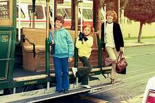 Vintage photo from the eighties featuring a mother and her children on a trolley-car in San Francisco, USA.