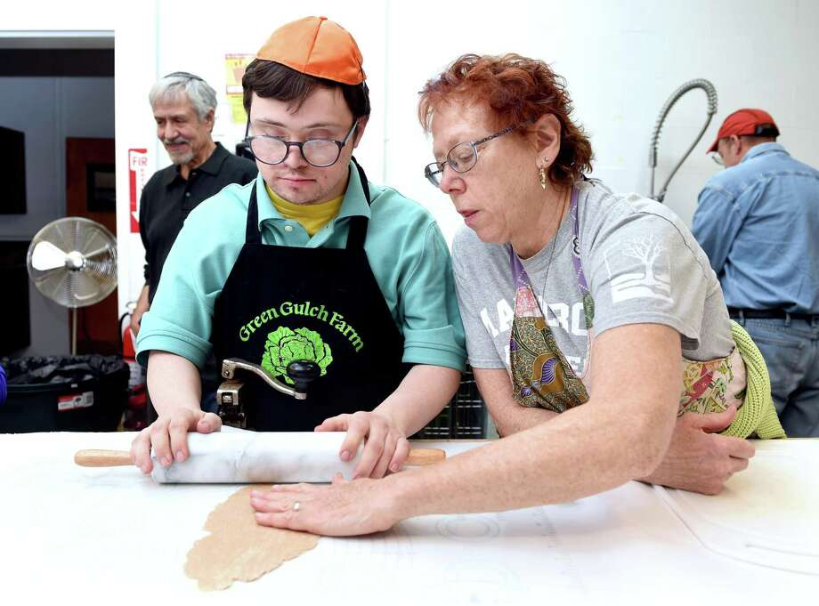 Jacob Botwick-Ries (left) of New Haven gets assistance from his mother, Jennifer Botwick, as he rolls out dough for wheat matzo in the kitchen of Congregation Beth El-Keser Israel in New Haven on April 19, 2019. The matzo is for the Jewish holiday of Passover which requires Jews to eat unleavened bread. Photo: Arnold Gold / Hearst Connecticut Media / New Haven Register