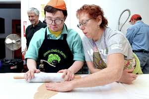 Jacob Botwick-Ries (left) of New Haven gets assistance from his mother, Jennifer Botwick, as he rolls out dough for wheat matzo in the kitchen of Congregation Beth El-Keser Israel in New Haven on April 19, 2019. The matzo is for the Jewish holiday of Passover which requires Jews to eat unleavened bread.