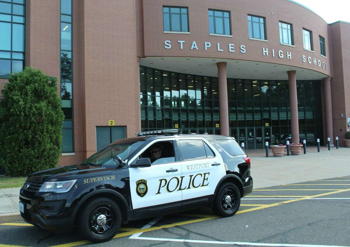 A Westport police car sits outside Staples High School.