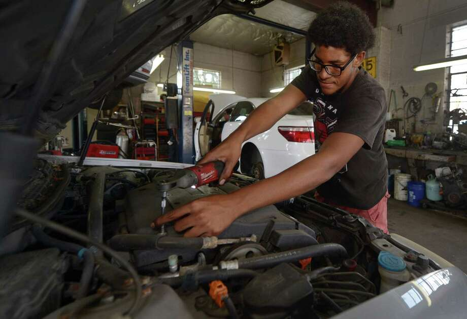 As a participant in the Mayor's Summer Youth Employment Program, Clive Bey is learns auto mechanics Wednesday, July 11, 2018, at Longo's Auto Repairs on South Water Street in Norwalk, Conn. The program has received over 400 applications this year. Photo: Erik Trautmann / Hearst Connecticut Media / Norwalk Hour