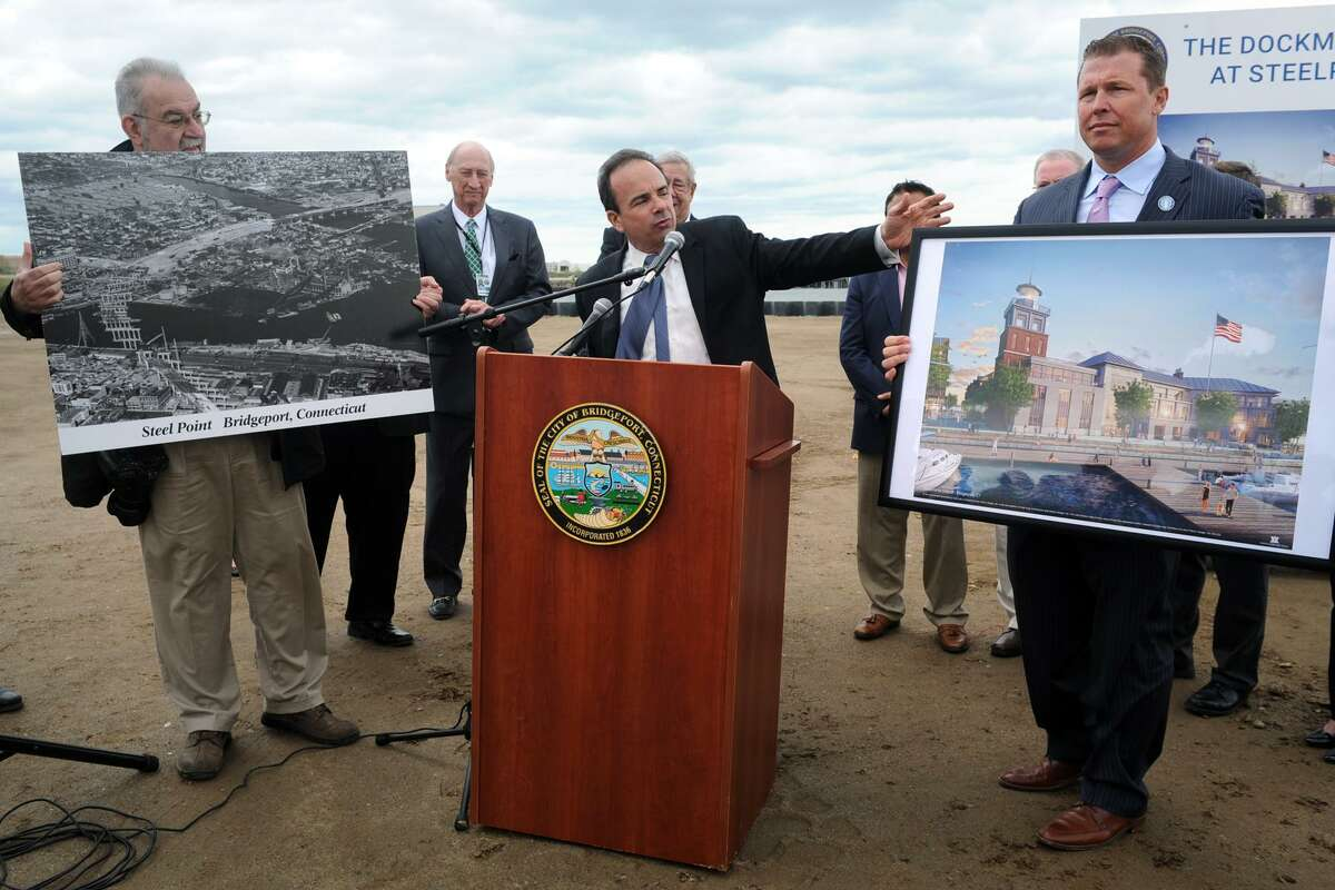 Mayor Joe Ganim speaks at a groundbreaking ceremony for the waterfront development portion of Steelpointe Harbor, in Bridgeport, Conn. May 15, 2015. The mayor is joined here by developer Robert Christoph, Jr., right, Executive Vice President of Bridgeport Landing Development, and Frank Gerratana, left, who holds an aerial photograph of the area shot in the 1950's.