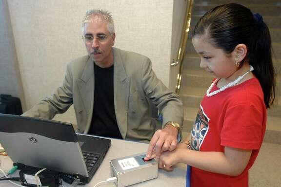 Ted Carlino, National Program Director for Operation Kidsafe, fingerprints Jasmine Garcia, 9, during the Operation Kidsafe National Safety Tour at Goodson Honda North.
