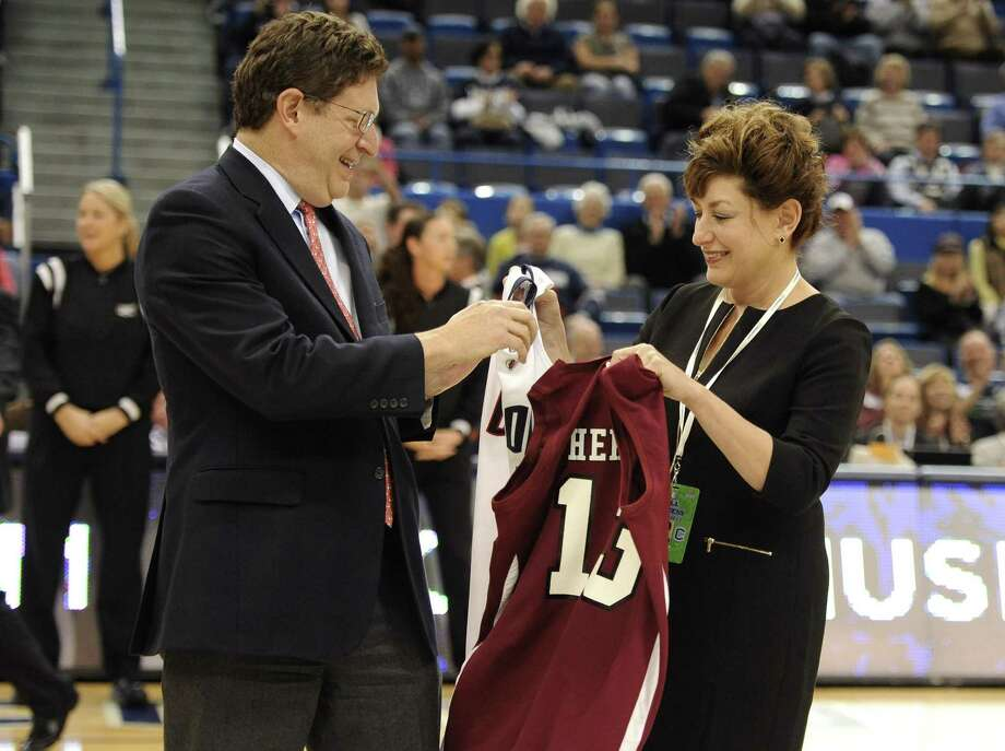 UConn president Susan Herbst, right, exchanges a team jersey with her brother, Jeffrey Herbst, Colgate's president, before a game on Nov. 28, 2012. Photo: Jessica Hill / Associated Press / FR125654 AP