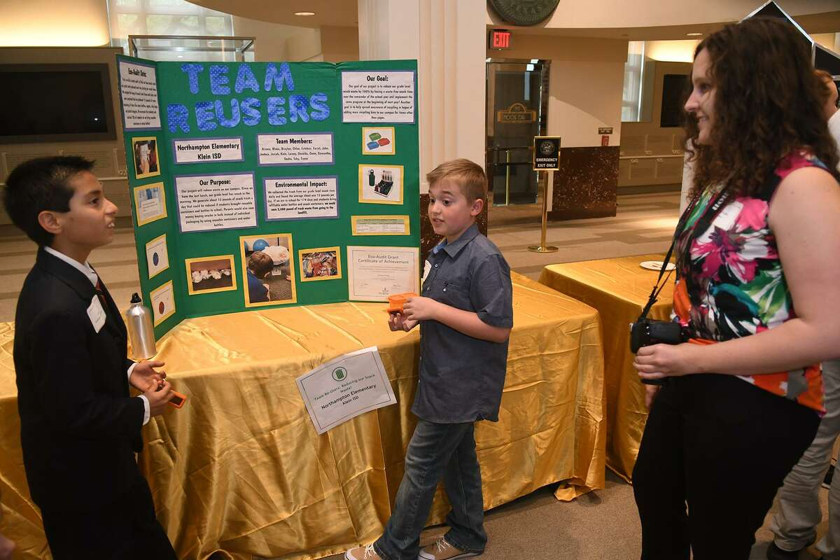 """John Martinez, 10, from left, and Braylon Selman, 10, both 4th graders at Northhampton Elem., discuss their team's """"Team Reuser"""" environmental audit project with Lauren Fuller of EcoRise during the inaugural Houston Student Innovation Showcase held in The Legacy Room at City Hall in Houston on April 17, 2019."""