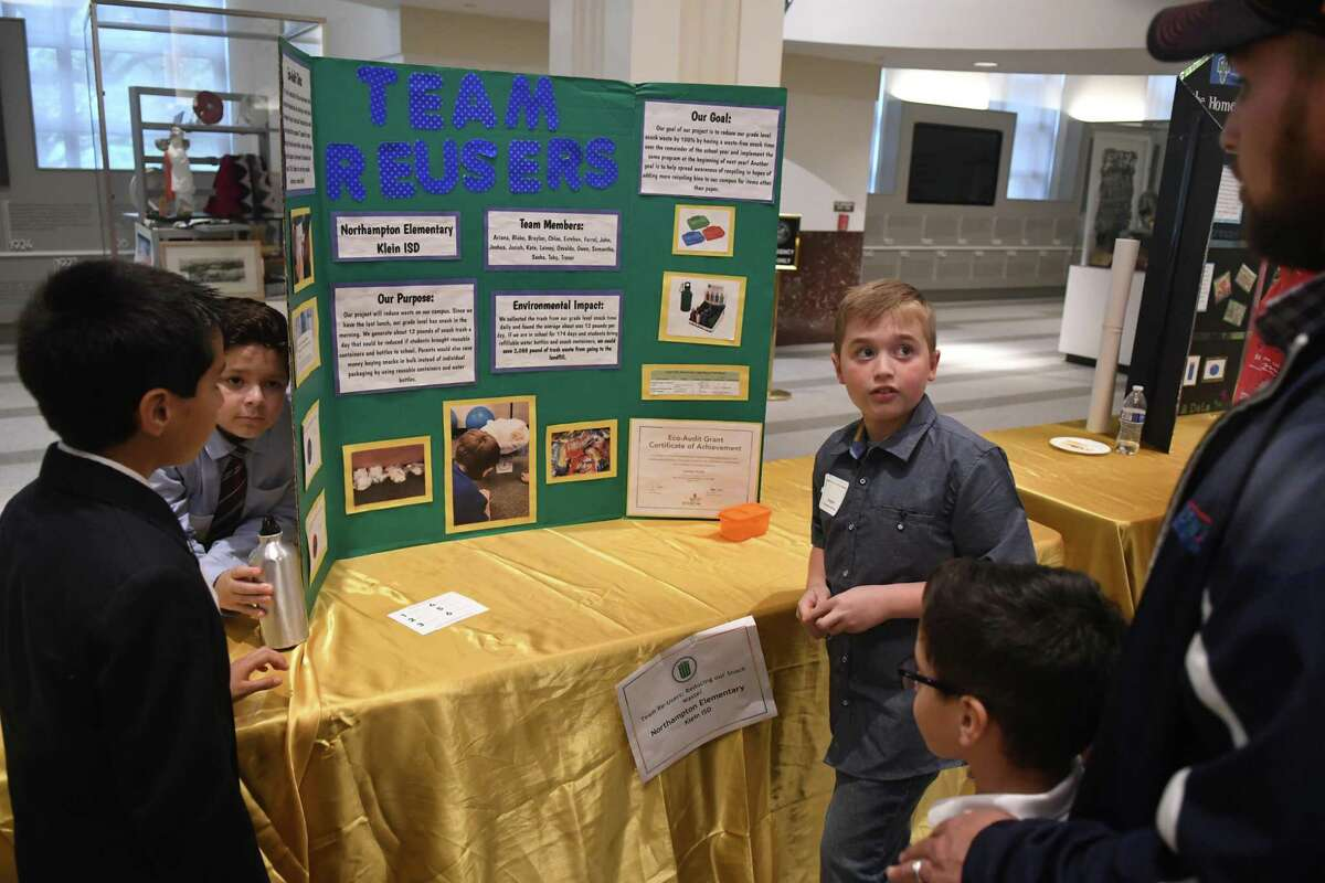 """Braylon Selman, 10, right, a 4th grader at Northhampton Elem., discusses his team's """"Team Reuser"""" environmental audit project with a visitor during the inaugural Houston Student Innovation Showcase held in The Legacy Room at City Hall in Houston on April 17, 2019."""