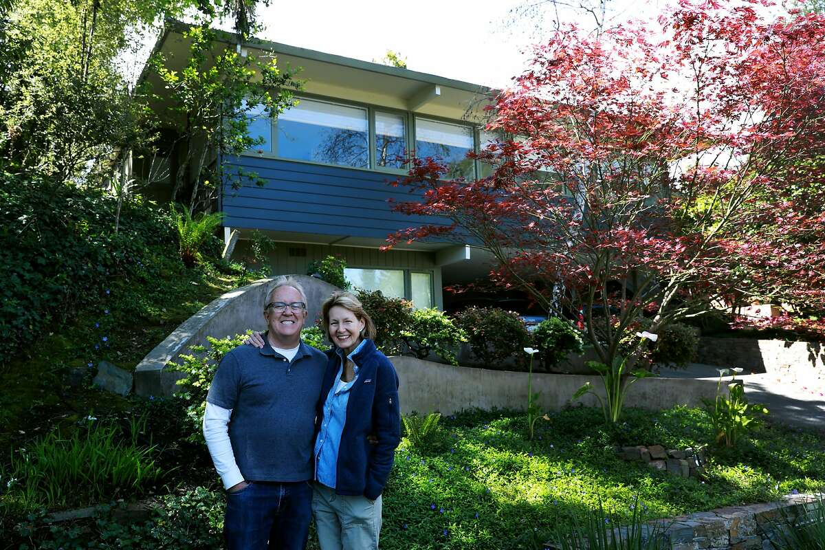 Michael and Alison Downs pose for a photo in front of their home in Berkeley, Calif., on Saturday, April 13, 2019. When the couple bought their home to be close to their kids, they didn't think they'd have any trouble getting insurance. But Michael's insurer since 1977, State Farm, refused to insure the new house, in addition to a dozen other companies. He got a policy from Travelers for more money. The insurance company also required him to switch all his coverage for his car and personal liability umbrella.