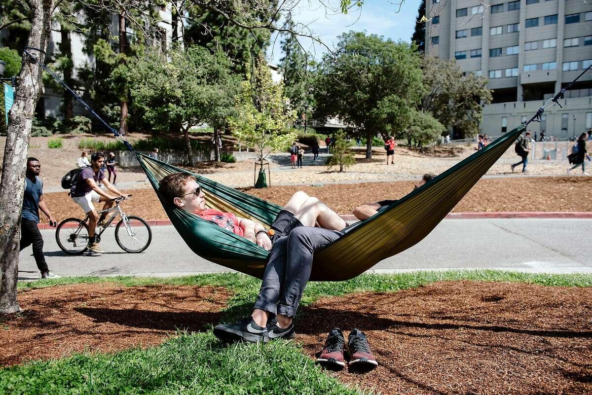UC Berkeley civil engineering masters students Homero De Toledo, left, and Mauricio Clark relax in a hammock on the Cal campus in Berkeley, Calif, on Friday, April 19, 2019.