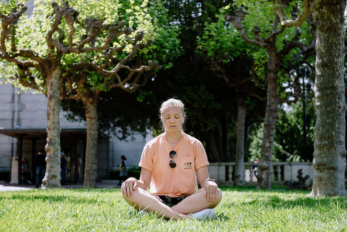 UC Berkeley sophomore student Maja Ahmann takes 5 minutes for a quick meditation using the app Headspace, in a quiet spot on the Cal campus in Berkeley, Calif, on Friday, April 19, 2019.