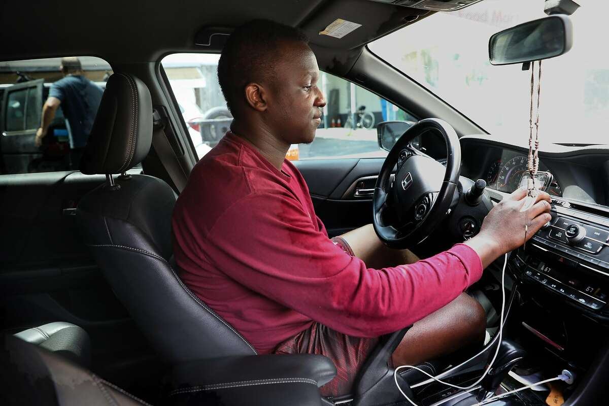 Cal state student and Lyft driver Mathayo Huma from Hayward checks for rides at the beginning of his shift at a Shell station on 5th St. on Friday, April 19, 2019, in San Francisco, Calif.