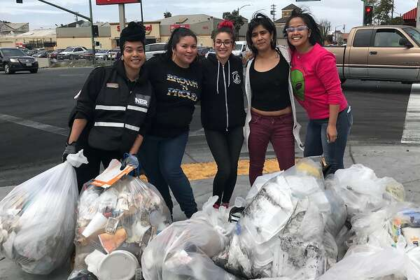 From left to right, Ginger Cuevas, Crystal Lucero, Yasmin Arreola, Diana Garcia and Yanira Cortez picked up trash left after a sideshow in Oakland's Fruitvale District.