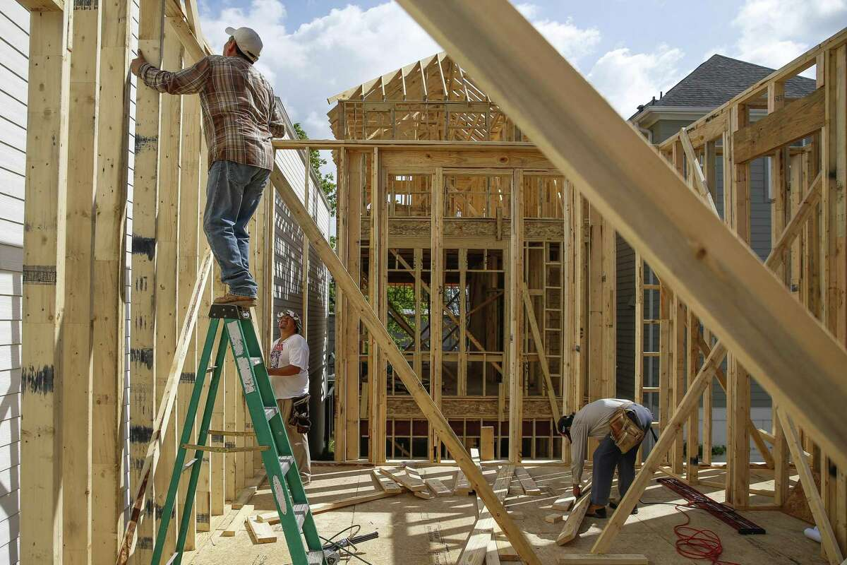 Immigrant construction workers, who all moved here from Mexico, build a house in 2017 off West 23rd Street in Houston.