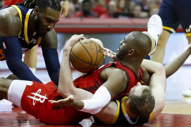 Houston Rockets guard Chris Paul (3) tries to call for a timeout while battling for a loose ball with Utah Jazz forward Jae Crowder (99) and forward Joe Ingles (2) the second half of game 2 during the NBA playoffs at the Toyota Center in Houston, Wednesday, April 17, 2019.