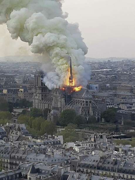 "Flames and smoke rise from the blaze at Notre Dame cathedral in Paris, Monday. An inferno that raged through Notre Dame Cathedral for more than 12 hours destroyed its spire and its roof but spared its twin medieval bell towers, and a frantic rescue effort saved the monument's ""most precious treasures,"" including the Crown of Thorns purportedly worn by Jesus, officials said Tuesday."