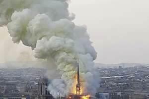 """Flames and smoke rise from the blaze at Notre Dame cathedral in Paris, Monday. An inferno that raged through Notre Dame Cathedral for more than 12 hours destroyed its spire and its roof but spared its twin medieval bell towers, and a frantic rescue effort saved the monument's """"most precious treasures,"""" including the Crown of Thorns purportedly worn by Jesus, officials said Tuesday."""