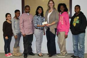 St. Luke's student Sheetal Akole, middle, presents a check to help fund the after-school program to Jennifer Barahona, director of youth development at Family & Children's Agency. Barahona is now going to be the new chief executive officer for Norwalk ACTS.