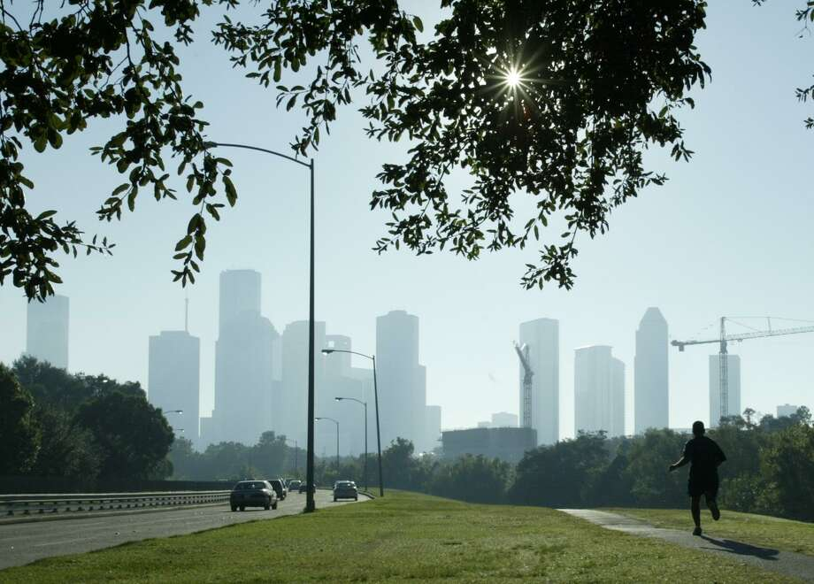 A jogger gets in his morning workout along Memorial Drive as smog obscures the view of downtown Houston in this file photo from 2003. The Houston/Beaumont/Port Arthur areas are set to be under an ozone warning on Saturday, April 20, 2019. Photo: Buster Dean,  Staff / Houston Chronicle / Stratford Booster Club