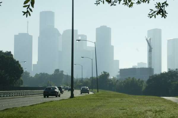 A jogger gets in his morning workout along Memorial Drive as smog obscures the view of downtown Houston in this file photo from 2003. The Houston/Beaumont/Port Arthur areas are set to be under an ozone warning on Saturday, April 20, 2019.