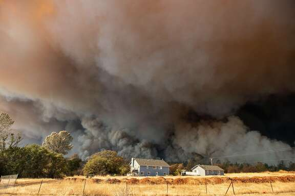 (FILES) In this file photo taken on November 8, 2018 a home is overshadowed by towering smoke plumes as the Camp fire races through town in Paradise, California. The Trump administration is planning to slash firefighting assistance payments to the state. (Photo by Josh Edelson / AFP)JOSH EDELSON/AFP/Getty Images