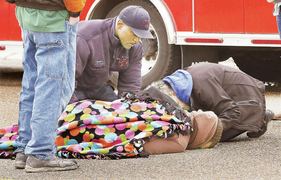 A passerby, who got down on all fours, talks to and comforts a man laying face down on East Broadway at Miami Street Friday after he was struck by a car in the westbound lanes of the roadway. The good samaritan stayed with the man keeping him talking for several minutes until the first Alton Fire Department paramedics, including Engineer Donald Holliday, left, arrived on the scene. Initial police broadcasts were that the man ended up in the roadway as part of a domestic dispute with someone before being hit by a driver who was apparently just in the wrong place at the wrong time. His injuries did not appear to be life-threatening.